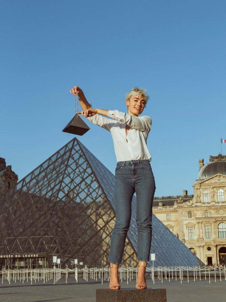 Elsa Muse portant le sac Cléo devant la pyramide du Louvre